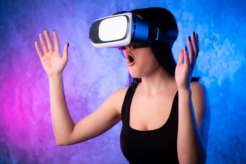 Undra den unga kvinnan i virtuell verklighetexponeringsglas över kulör bakgrund för neon Chockad flicka som bär VR-apparaten Närb arkivfoton