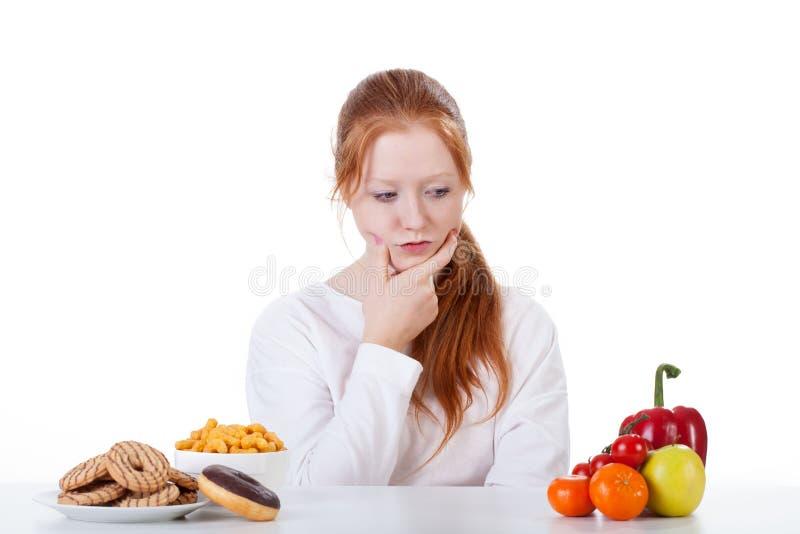 Undra huruvida som äter sötsaker eller grönsaker arkivbilder