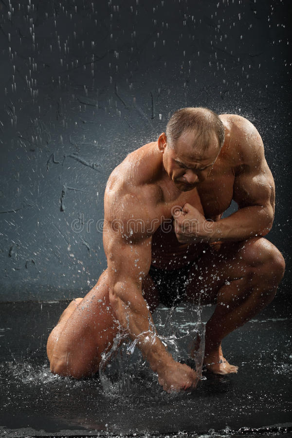 Undressed bodybuilder in rain hits water by hand royalty free stock photo