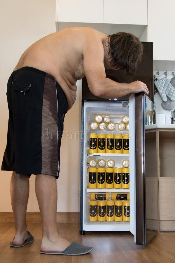 Undressed fat man opens the fridge full of cans stock photos