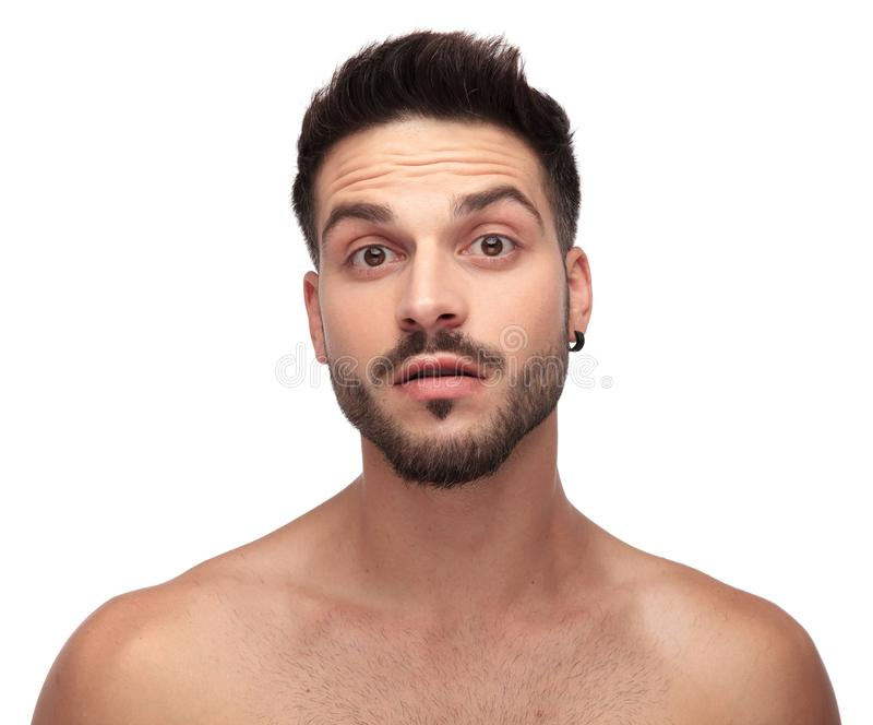 Undressed man with beard looking curious with big eyes royalty free stock image
