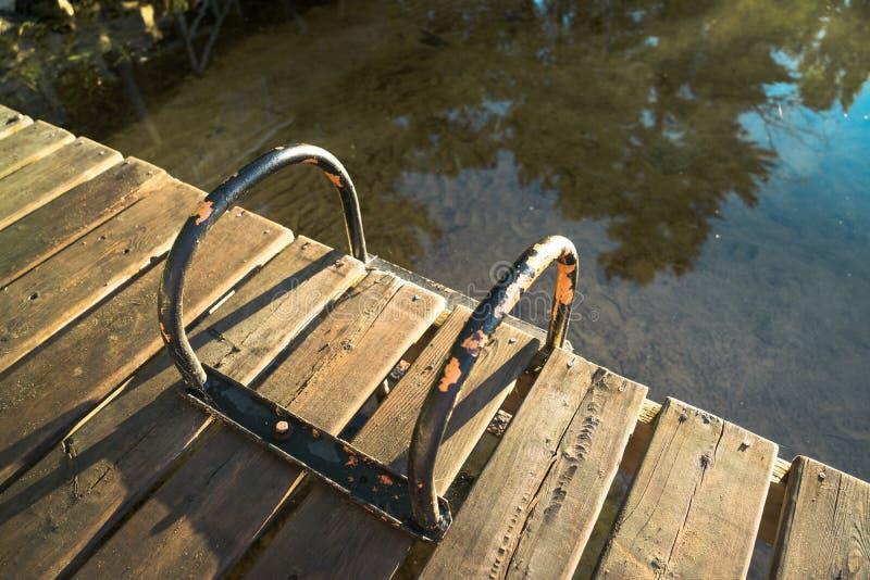 Une échelle usée de dock de bord de lac, regardant vers le bas photo stock