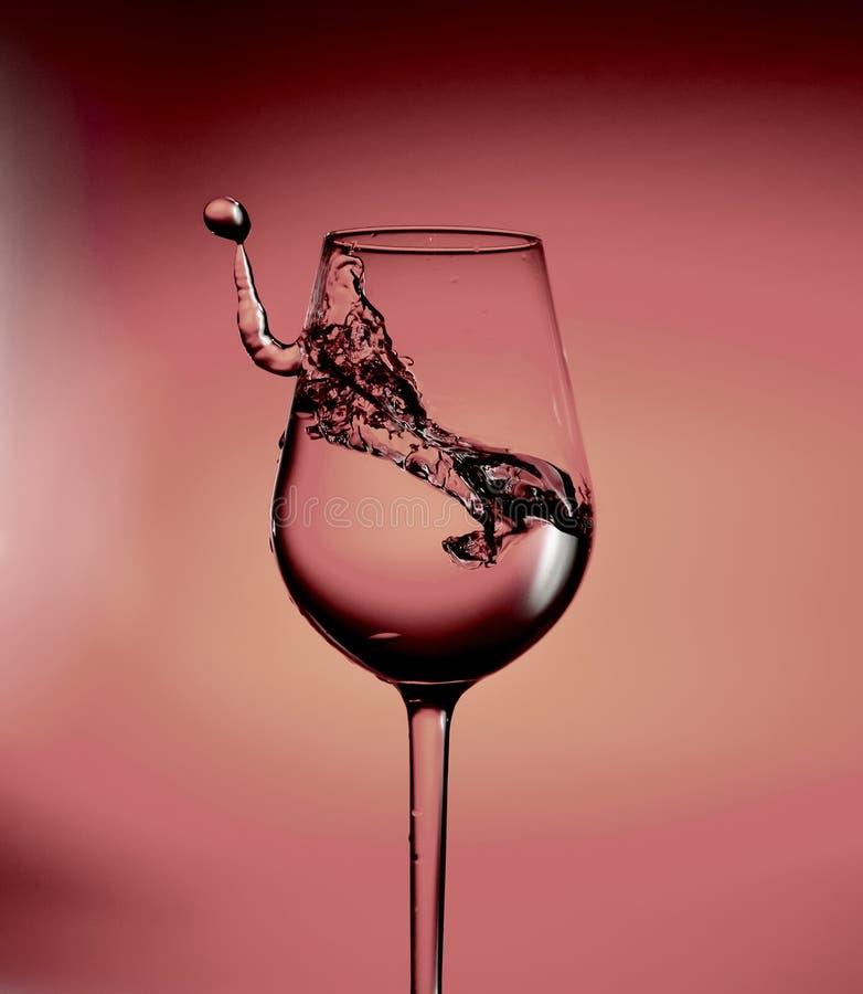 Une éclaboussure de l'eau dans un verre et une baisse Dans des tons cramoisis mouvement photo libre de droits