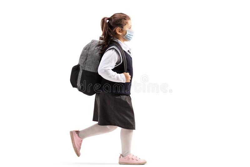 Une écolière avec un sac à dos portant un masque de protection et une marche image stock
