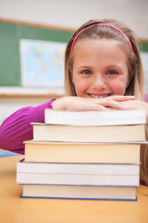 Une écolière de sourire posant avec une pile de livres photos libres de droits