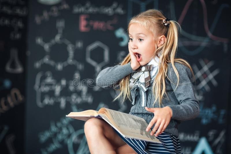 Une écolière douce de fille s'assied sur un tableau avec le fond de formules d'école Travail de travaux en lisant un livre stupéf photos stock