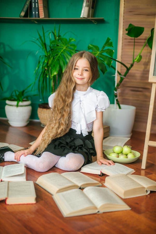 Une écolière douce des classes juniors avec de longs cheveux blonds avec des livres, un conseil pédagogique et des pommes photo stock
