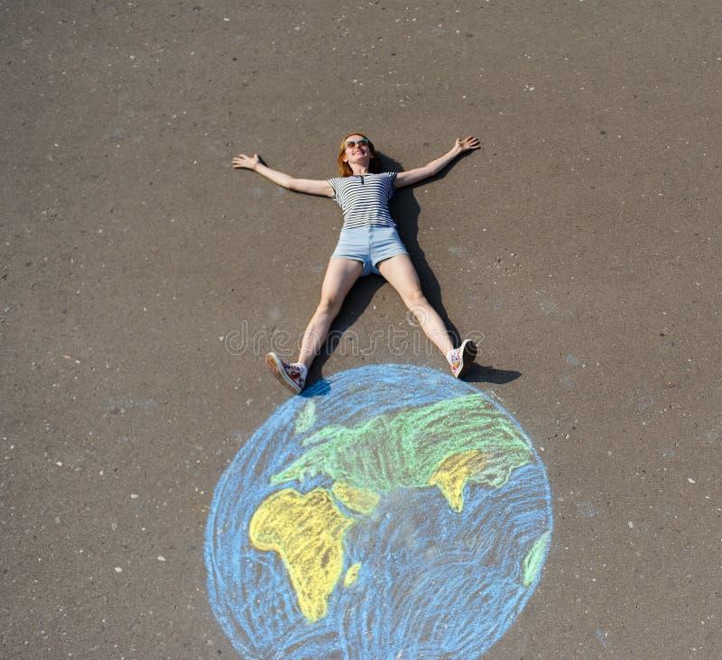 Une écolière sur une sphère de terre dessinée à la craie sur un asphalte images stock