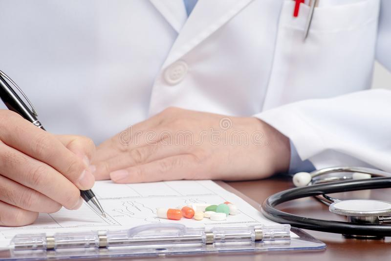 Une écriture masculine de docteur sur la forme médicale avec le stéthoscope voisin photos stock