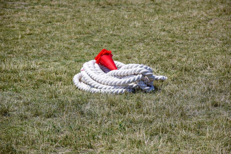 Une épaisse corde blanche tressée se trouve sur l'herbe brûlée du stade de l'école Les capuchons en plastique rouge restrictif so photo stock