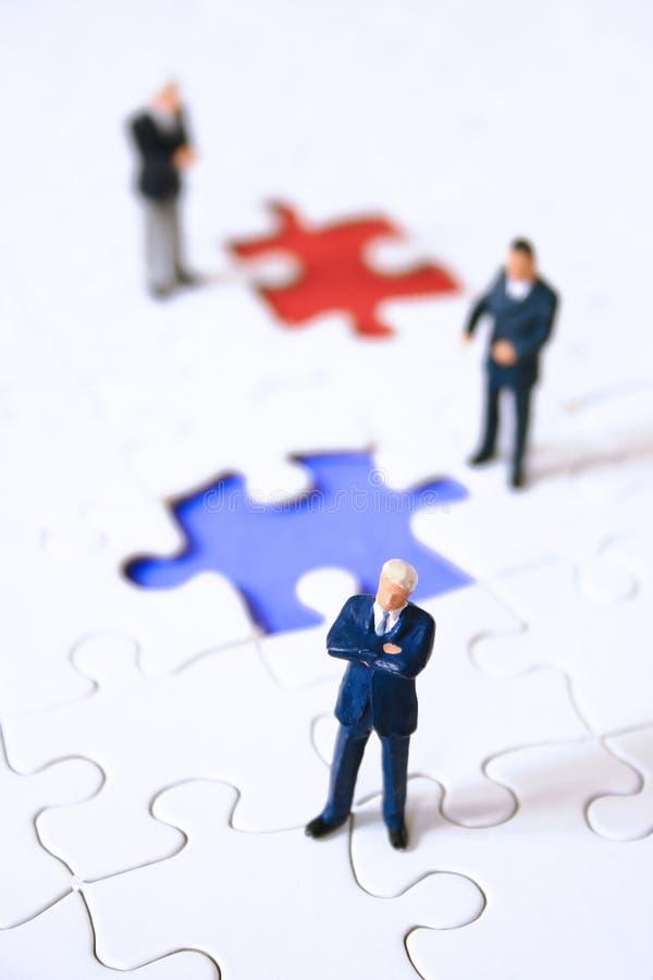 Une équipe d'affaires autour d'un puzzle photos stock