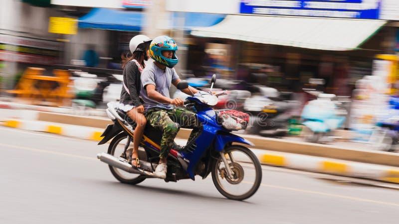 Une équitation de garçon et de fille sur une moto Mouvement brouillé images stock