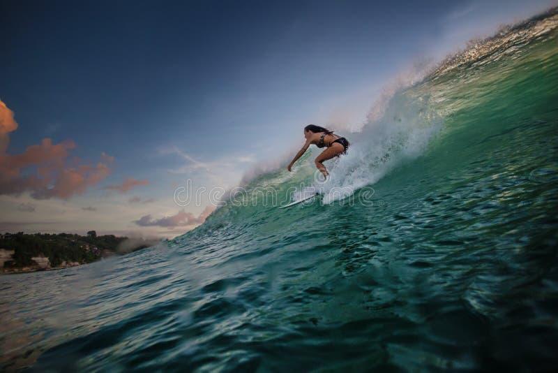 Une équitation de surfer sur le ressac vert image stock