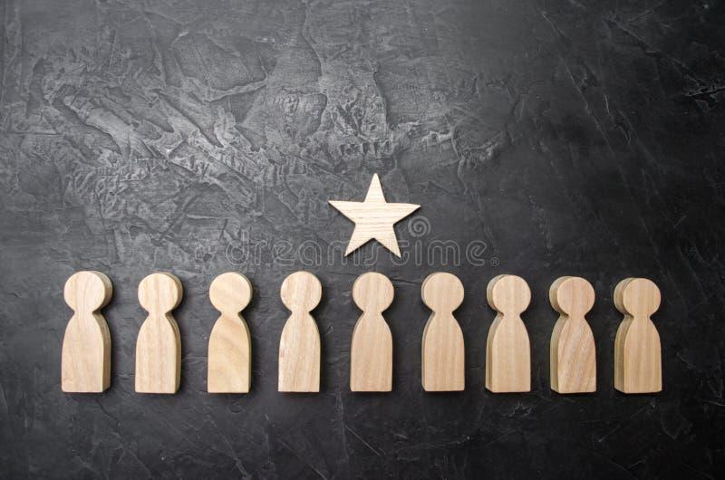 Une étoile au-dessus d'une personne qui se tient dans une rangée entre d'autres personnes Figurines en bois Le concept d'un signe image stock
