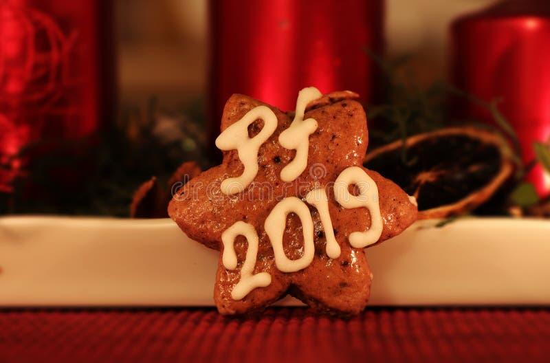 Une étoile faite maison de pain d'épice couverte de glaçage blanc et de souhaiter à vous PF 2019 Dans le chandelier de Noël de fo photographie stock