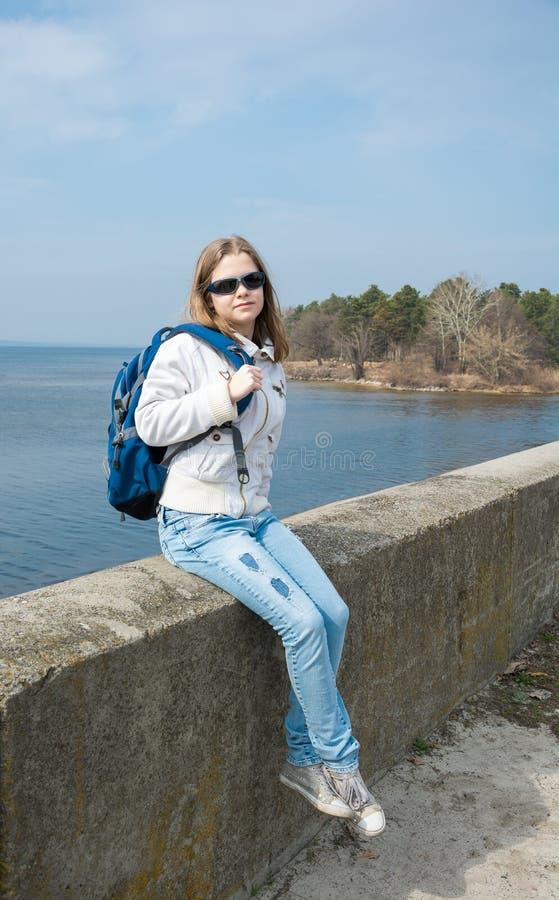 Une adolescente avec un sac à dos devant la mer photographie stock libre de droits