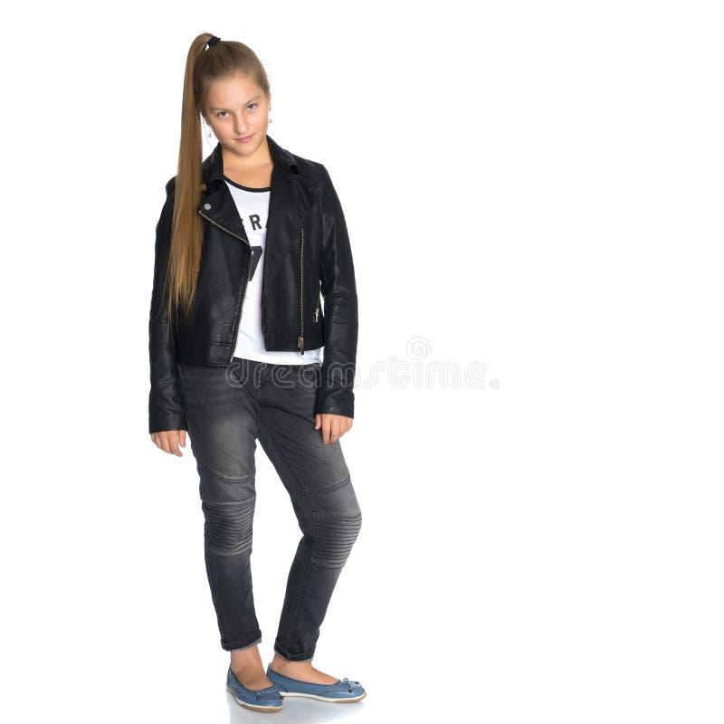 Une adolescente dans une veste en cuir et des jeans photo libre de droits