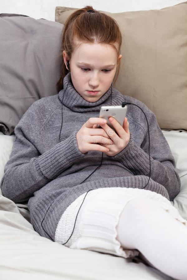 Une adolescente douce dans des écouteurs écoutant la musique image stock