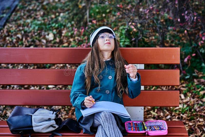Une adolescente en lunettes, un manteau et un chapeau tricoté assis sur un banc dans le parc dessine un dessin sur du papier Ferm photographie stock libre de droits