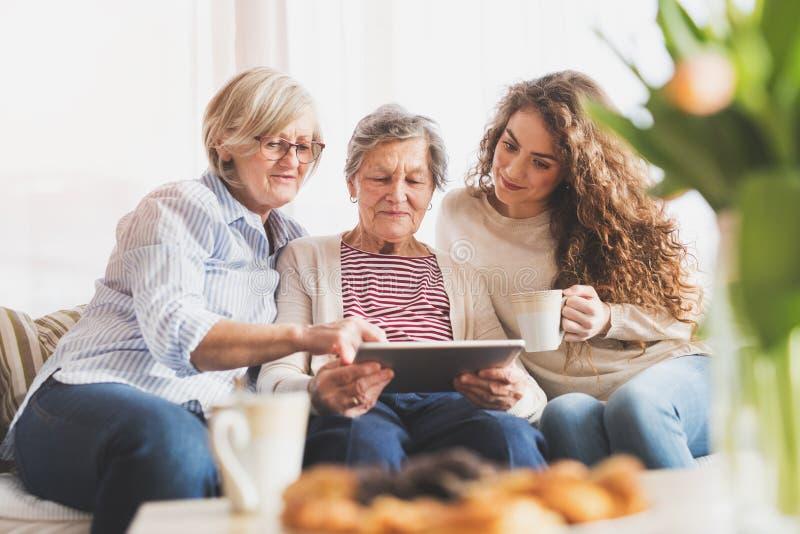 Une adolescente, une mère et une grand-mère avec le comprimé à la maison photos stock