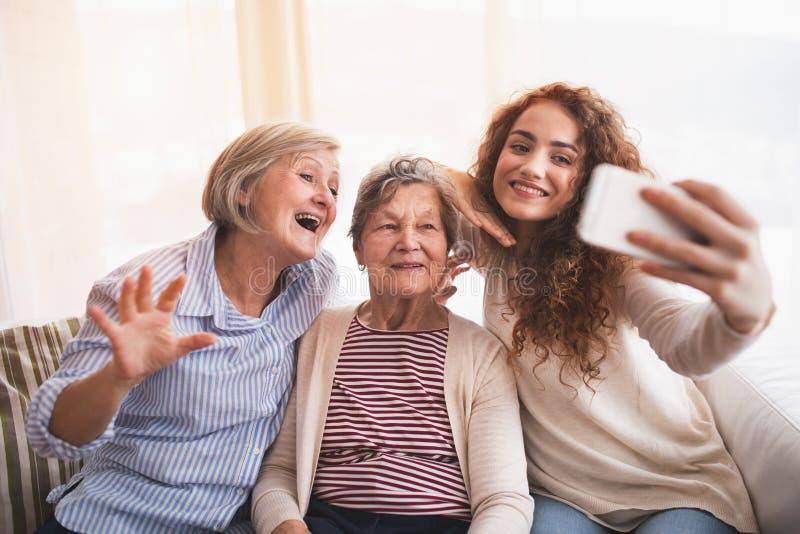 Une adolescente, une mère et une grand-mère avec le smartphone à la maison image stock