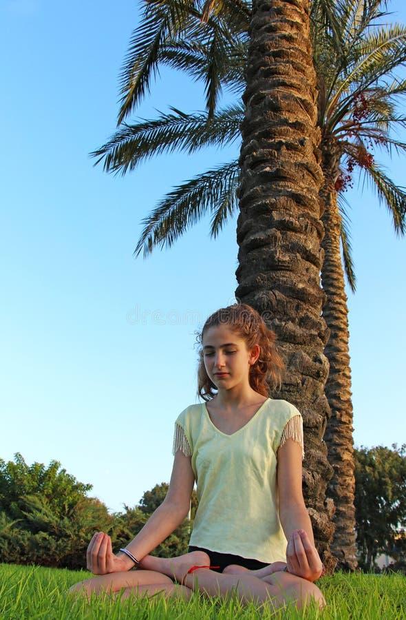 Une adolescente s'assied sur une pelouse et médite images libres de droits