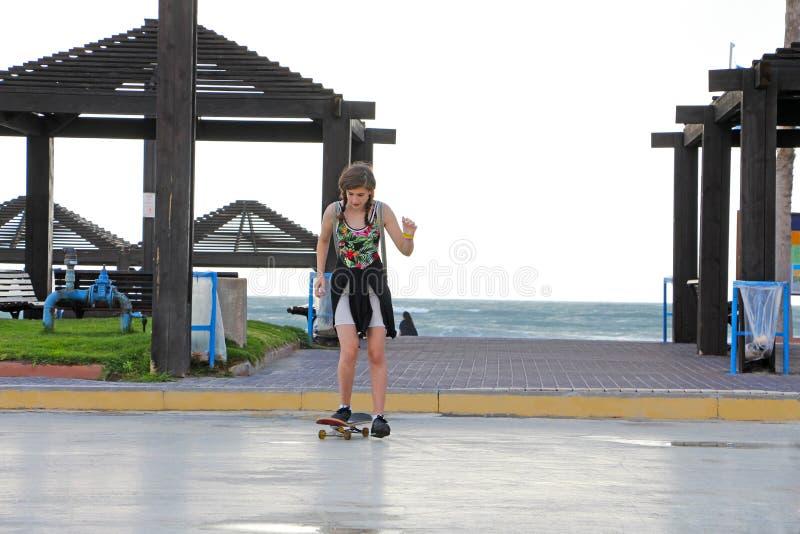 Une adolescente sur une planche à roulettes photographie stock libre de droits