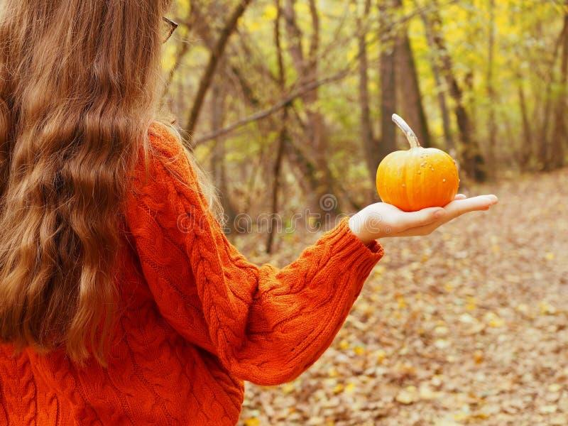 Une adolescente tenant un potiron dans sa main marchant dans la forêt images stock