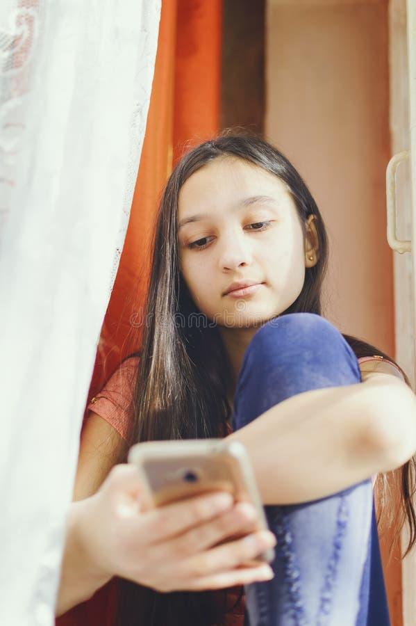 Une adolescente tient un téléphone portable photographie stock libre de droits