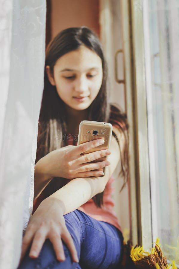 Une adolescente tient un téléphone portable plan rapproché, foyer mou photos libres de droits