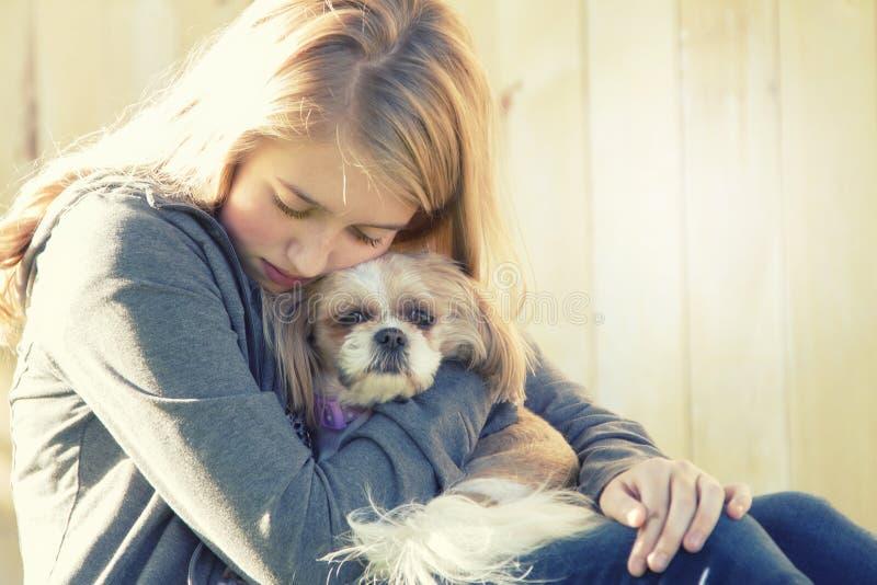 Une adolescente triste ou déprimée étreignant un petit chien photos stock
