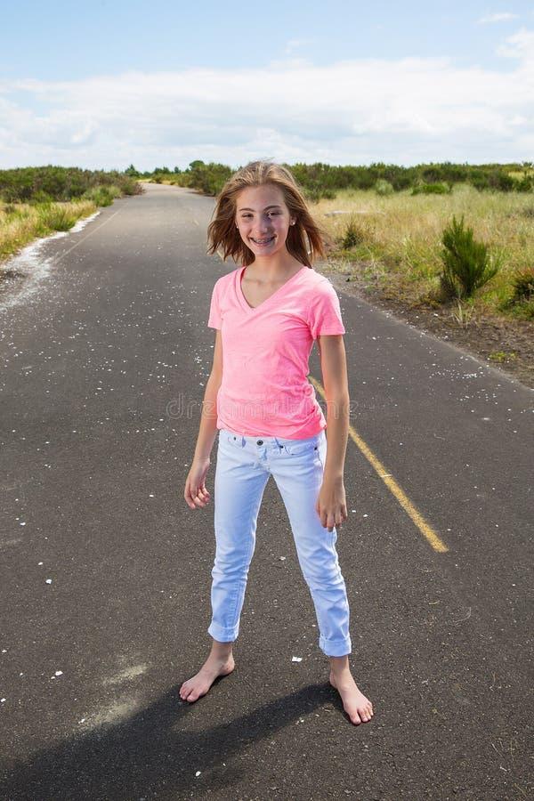 Une adolescente voyage nu-pieds sur une route vide photo stock