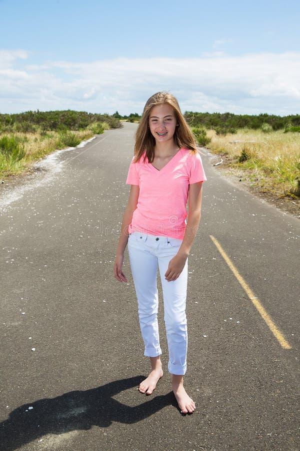 Une adolescente voyage nu-pieds sur une route vide photo libre de droits