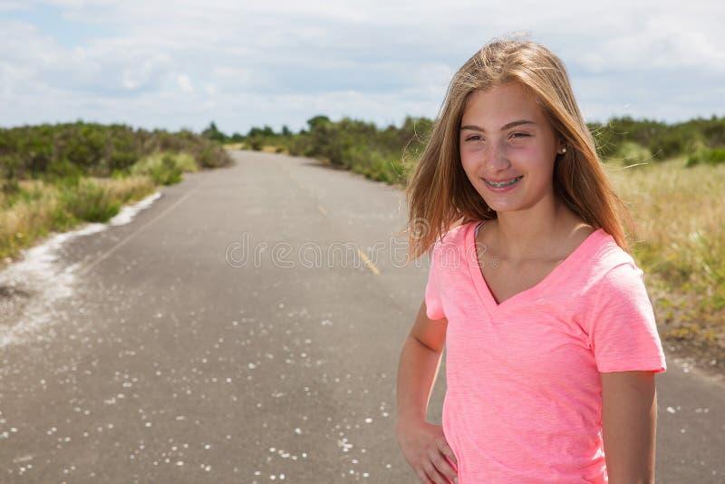 Une adolescente voyage nu-pieds sur une route vide photographie stock