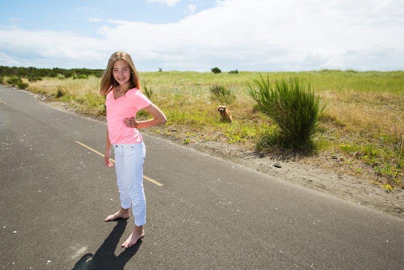 Une adolescente voyage nu-pieds sur une route vide photographie stock libre de droits