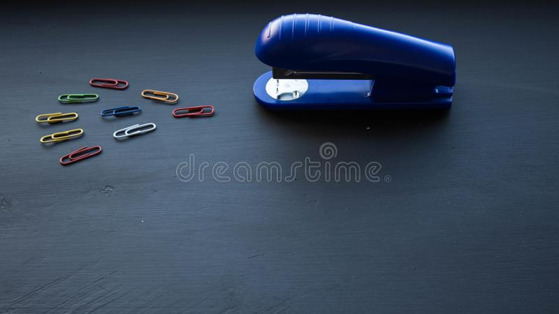 Une agrafeuse et des agrafes colorées sur le fond noir photos stock