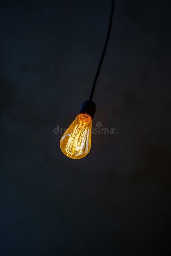 Une ampoule incandescente contre un mur gris Fin rougeoyante lumineuse de filament  photographie stock libre de droits
