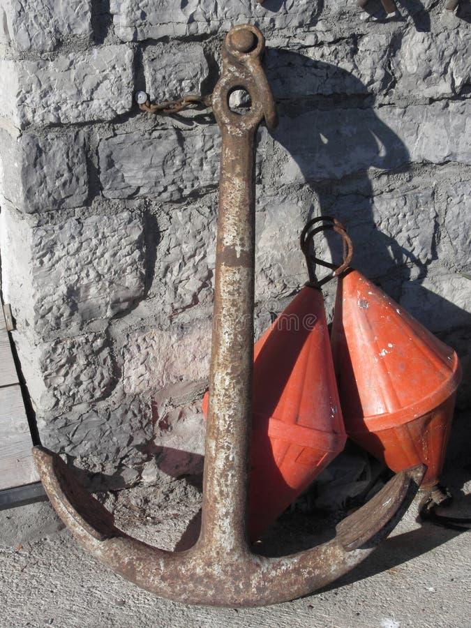 Une ancre rouillée et deux balises coniques oranges à la marina photo libre de droits