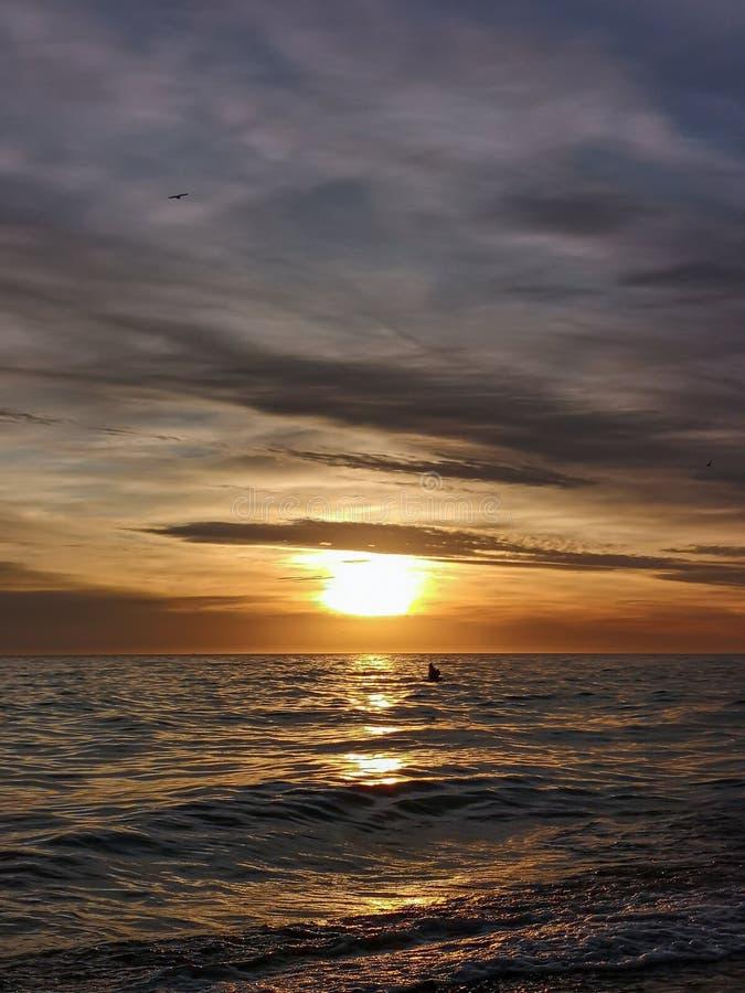 Une aube d'éblouissement traversant la mer photos stock