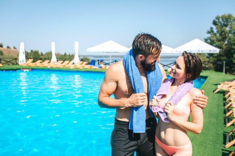 Une autre photo des couples bien construits et minces se tenant ensemble au bord de la piscine Ils regardent l'un l'autre photos libres de droits