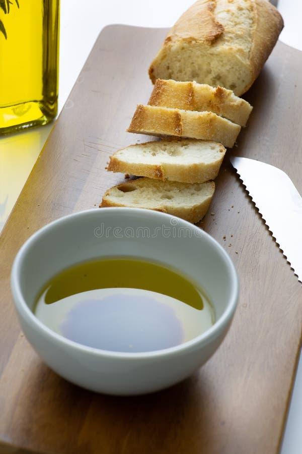 Une baguette de pain français coupée en tranches sur une planche à découper avec une cuvette d'huile d'olive avec une éclaboussur photographie stock