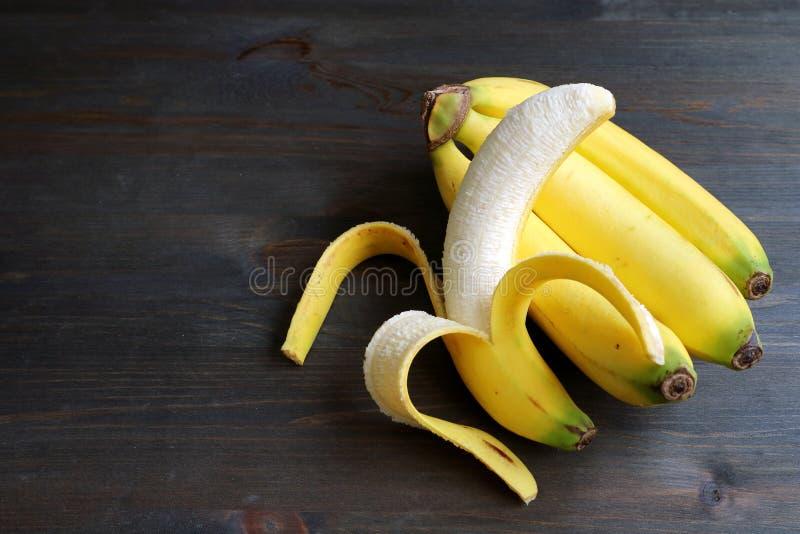 Une banane épluchée sur un groupe de bananes d'isolement sur la table en bois brune foncée photographie stock libre de droits
