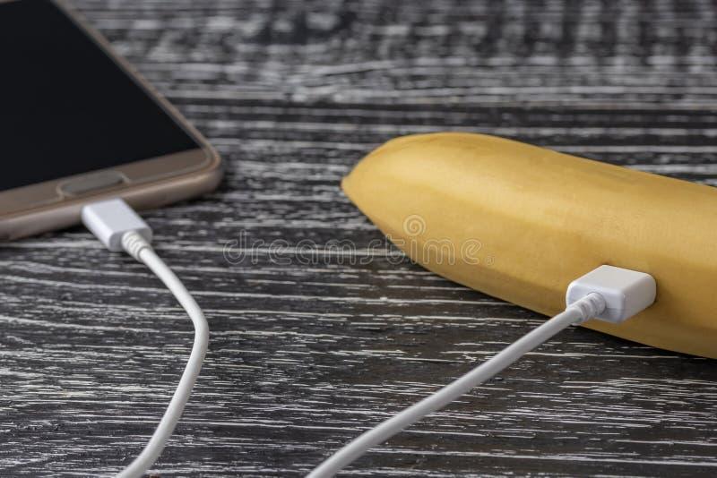 Une banane mûre fraîche est reliée au téléphone portable d'écran tactile à un câble blanc d'usb image libre de droits