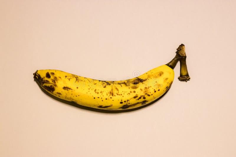 Une banane mûre sur le fond pulvérulent Fond en pastel photographie stock