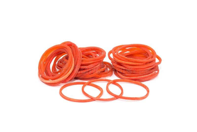 Une bande élastique rouge Pile des bandes élastiques avec le rubberband seul se tenant au-dessus du fond blanc photo stock