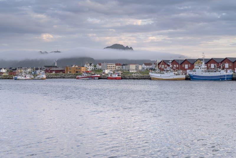 Une banque de brouillard peu profonde arrive sur le port du village à la tombée de la nuit, à Andenes, en Norvège image stock