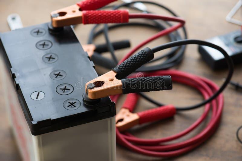 Une batterie de voiture avec la batterie rouge et noire Jumper Cables photos stock