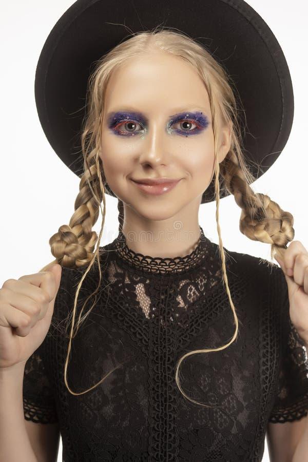 Une belle adolescente blonde de sourire portant une sorcière noire obtenue photo stock