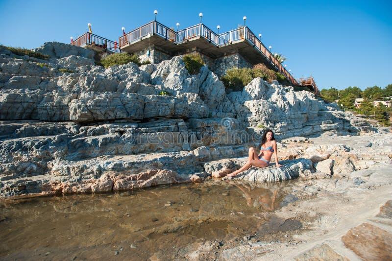 Une belle brune dans un bikini se repose sur une pierre Fille sexy de brune dans le bikini posant sur une plage images libres de droits