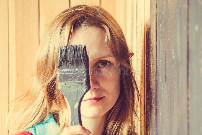 Une belle et jeune fille tient une brosse qu'elle a seulement peinte devant son visage photos libres de droits